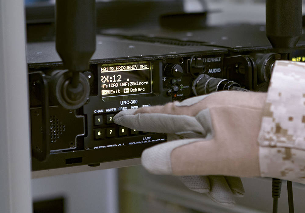 hand of solider pressing button on URC 300 Radio
